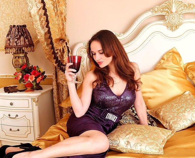 žena na posteli se sklenicí vína