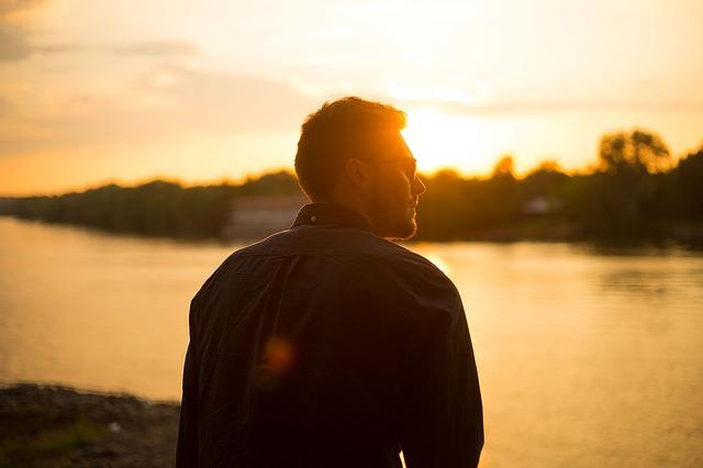 muž u řeky při západu slunce