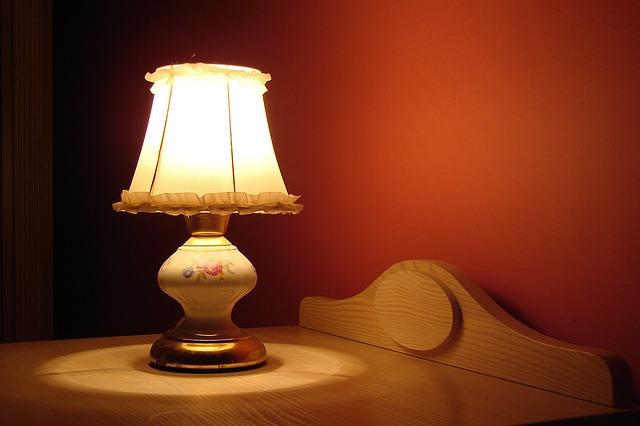 rozsvícená lampička na nočním stolku