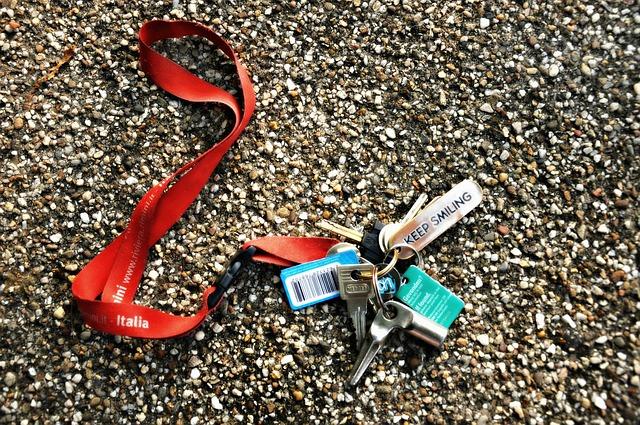 Klíčenka šňůrka s potiskem firmy a na ní připevněné klíče od domu