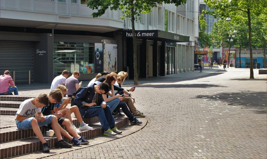 děti a studenti sedí venku u svých mobilních telefonů a surfují