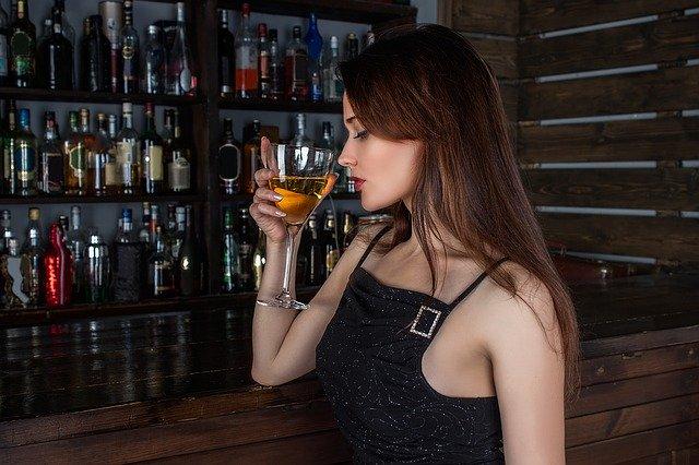 mladá žena pijící ze sklenice aperitiv v baru